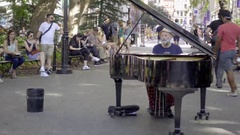 Pianist playing piano in park - panning across Washington Square Park - NYC 4K Stock Footage