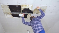 Man cleaning mold on ceiling.Ceiling panels damaged huge hole in roof from ra Stock Footage