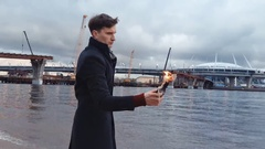Young man with a burning Molotov cocktail in hand standing on coast Stock Footage