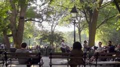 Woman pushing stroller man on laptop sitting Washington Square Park bench NYC Stock Footage