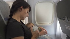 A mother feeds her child at the hands,  of the bottle in the airplane. Stock Footage