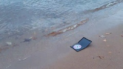 Data cd disc in fire on the sand at coast Stock Footage