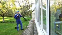 Man washing conservatory window with water jet reflecting on glass Stock Footage