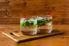 Two mojito cocktails with lime and mint in a glass on the table Kuvituskuvat