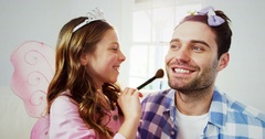 Girl dressed up in a fairy costume applying make-up on fathers face Stock Footage
