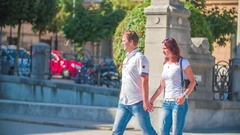 Walking hand in hand past the University of Ljubljana main building Stock Footage