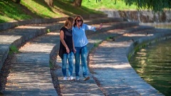 Two women are holding hands and walking on a river bank towards the water Stock Footage