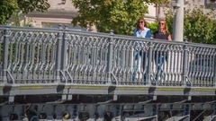 Two women are laughing and walking over a bridge Stock Footage