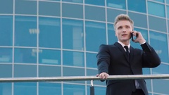 Smart business man talking on the phone and another business man also busy on Stock Footage
