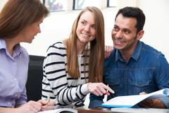 Couple With Financial Advisor Signing Document In Office Stock Photos