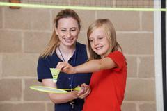 Teacher Giving Female Pupil Badminton Lesson Stock Photos