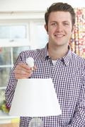 Man Putting Low Energy LED Lightbulb Into Lamp At Home Stock Photos
