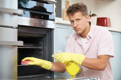 Fed Up Woman Cleaning Oven At Home Stock Photos