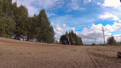 Country road, riding two tractor on the background of blue cloudy sky. Stock Footage