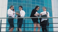 Four fair-skinned business women standing on terrace of office center and Stock Footage