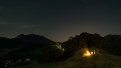 People sitting around campfire at starry moonlight night time lapse Stock Footage