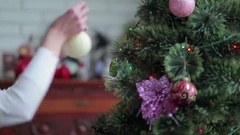 Pretty girl decorate Christmas tree with balls Stock Footage