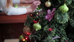 Two girls decorate Christmas tree in home Stock Footage