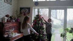 Two girls decorate Christmas tree near window Stock Footage