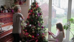 Two sisters decorating Christmas tree with a balls Stock Footage