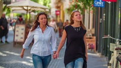 Two women are holding hands and are strolling around the city of Ljubljana Stock Footage