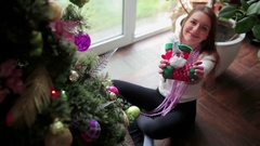 Beautiful girl show a Christmas toy and smiling Stock Footage