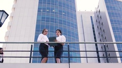 Two female coworkers talking outdoors during lunch time and a man coming out of Stock Footage
