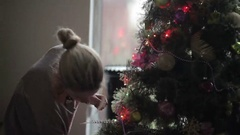 Young girl decorate Christmas tree near the window Stock Footage