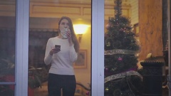 Girl standing near window and Christmas tree Stock Footage