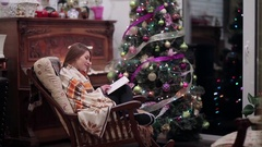 Girl under plaid read book near the Christmas tree Stock Footage