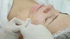 Woman middle-aged in spa salon with beautician. Botox injections Stock Footage
