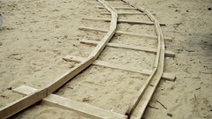 Rails from wood lying on the sand. HD Stock Footage