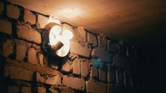 Incandescent Lamp Lights Up on a Stone Wall Stock Footage