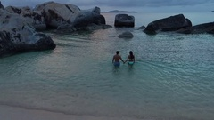Young couple holding hands at sunset in the water in Virgin Gorda Stock Footage