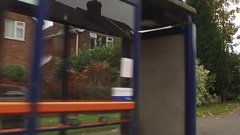 Slow motion panning shot of a bus stop, homes and street. Stock Footage