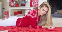 Young happy girl lying on red blanket next to fireplace Stock Footage