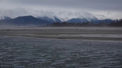 Windswept Wintry River Ice Flowing and Sandstorm with Distant Mountains HD Stock Footage