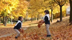 Two fashionable cute kids, throwing leaves in the park, having fun Stock Footage