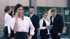 Pretty business lady is talking happily on the phone and her colleagues in the Stock Footage