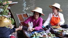 People on food boats at floating market  in river water. Bangkok, Thailand Stock Footage