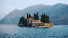 Little island with stone church on the sea before the mountains Stock Footage