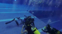 Instructor and two divers on bottom in pool underwater Stock Footage