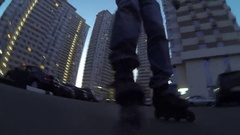 Legs of roller skater near residential buildings at summer evening Stock Footage