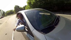 Man and woman ride in car, man holds stick and makes selfie Stock Footage
