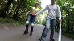 Man and woman roller skate in park, man makes selfie with stick Stock Footage
