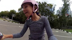 Happy girl in pink helmet rides bicycle and rises her knees Stock Footage