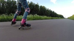 Happy girl in pink rollerblades roller skates on road at summer Stock Footage