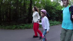 Man, woman and two children roller skate in green park, boy makes selfie Stock Footage