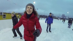 Woman make selfie and skate with man, two children among people on ice rink Stock Footage