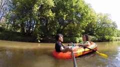 Couple (with model releases) sails on inflatable boat Intex Stock Footage